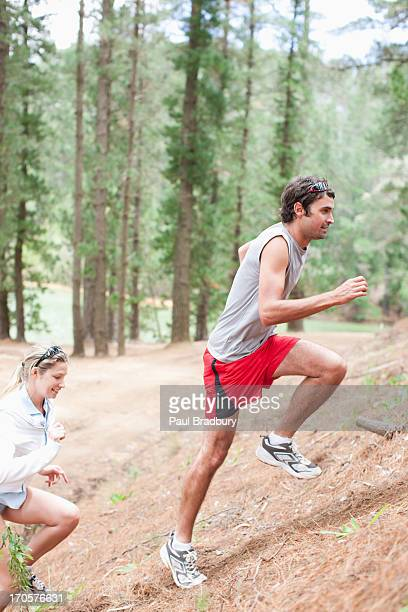Couple climbing hill in forest