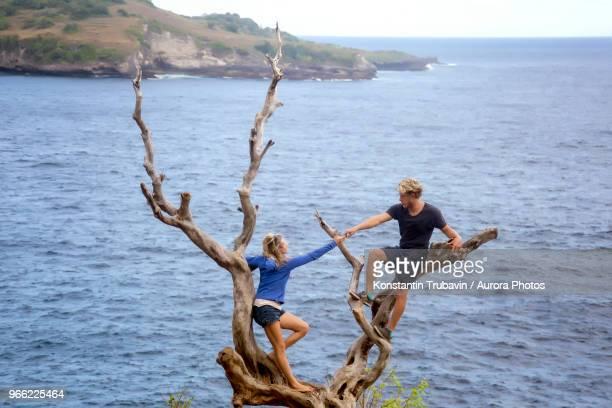 Couple climbing on bare tree on coastline, Nusa Penida, Bali, Indonesia