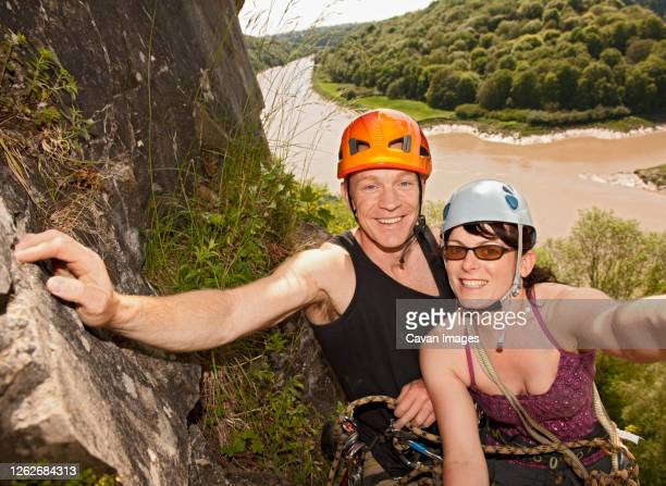 couple climbing steep rock face in south wales - individual event stock pictures, royalty-free photos & images