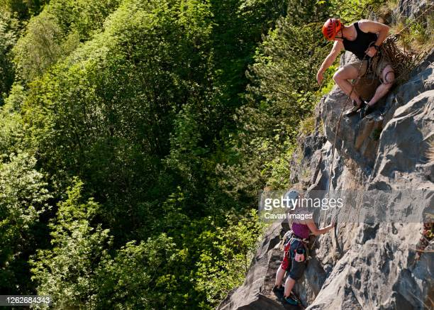 couple climbing steep rock face in south wales - couple relationship stock pictures, royalty-free photos & images