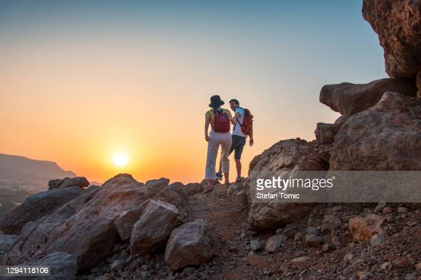 couple climbing to the mountain top in the uae desert at sunset - ras al khaimah stock pictures, royalty-free photos & images