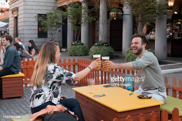 Couple clinking beers at an outdoor area set up for drinking at the Covent Garden, London. As the UK government lifted the restrictions imposed on...
