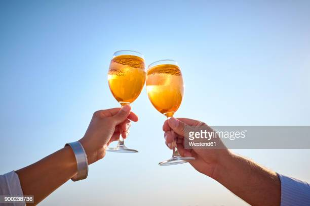 Couple clinking spritz glasses before blue sky