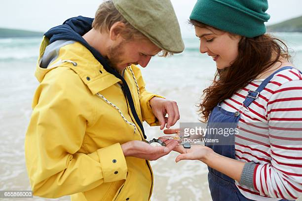 Couple collecting shells and stones at beach.