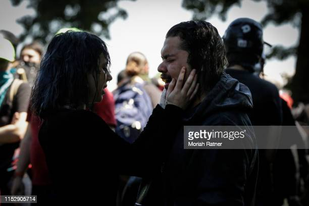 A couple comforts one another after cooling off in sprinklers at the Waterfront Park during an antifa demonstration on June 29 2019 in Portland...