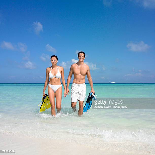 Couple coming out of ocean carrying flippers