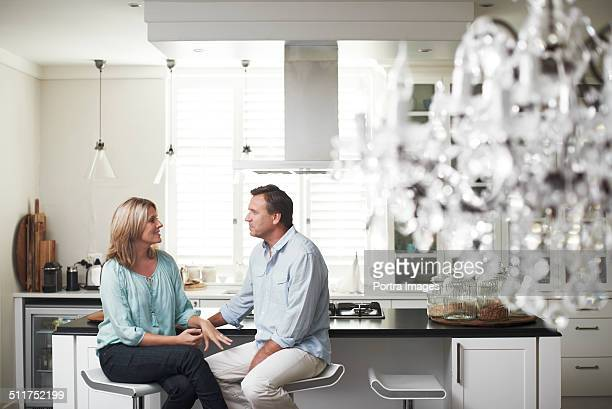Couple communicating on stools in kitchen