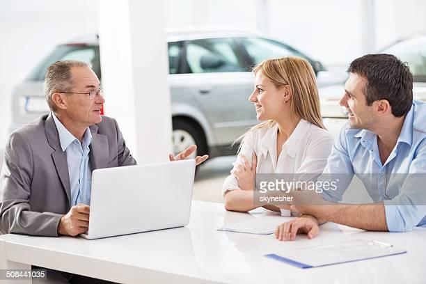 Pareja comunicarse con un vendedor de coches.