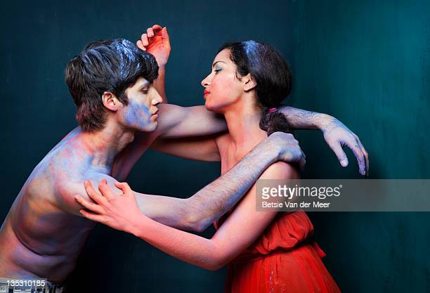 Couple connecting,covered in coloured powder.
