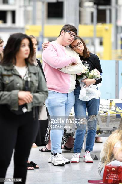 A couple console each other in front of the floral memorial at Victoria station during the commemoration People gather at Victoria station to mark...