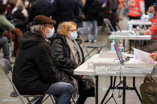 Couple consults a Red Cross health worker after having been vaccinated inside the Paris Stade de France following its conversion into a Covid-19...