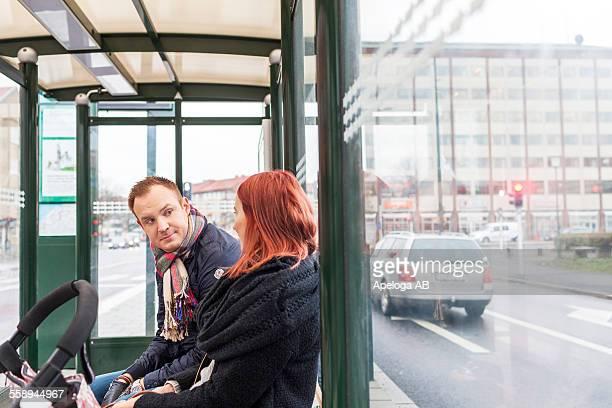 Couple conversing while waiting at bus stop