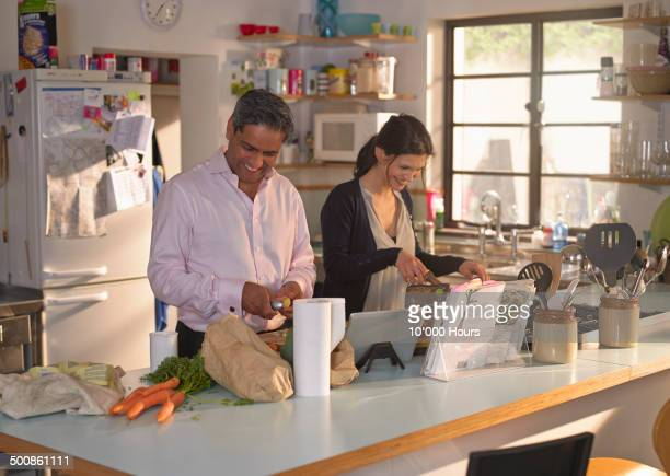 Couple cooking an evening meal from recipe on ipad