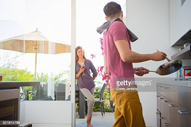 Couple cooking and drinking wine in kitchen