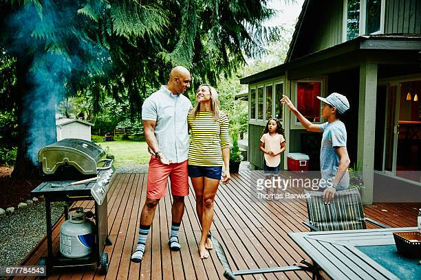 Couple cooking at barbecue in backyard with family