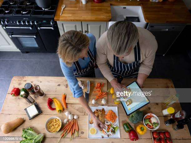 couple cooking at home following a recipe on a tablet computer - tutorial stock pictures, royalty-free photos & images