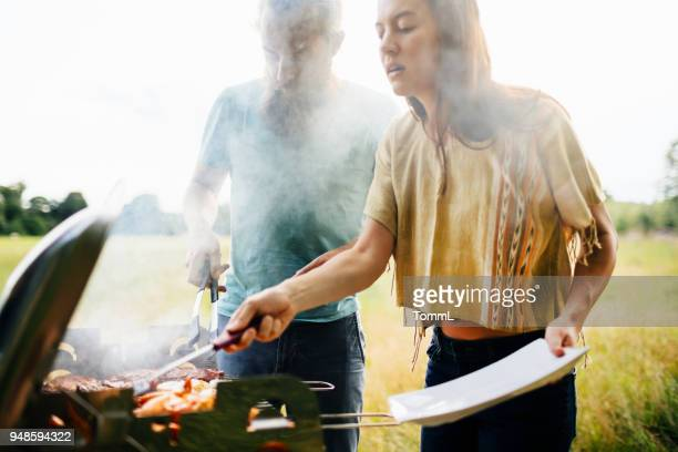 couple cooking food on bbq for friends - grilling stock pictures, royalty-free photos & images