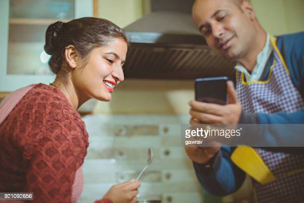 couple cooking food together in kitchen. - husband stock pictures, royalty-free photos & images