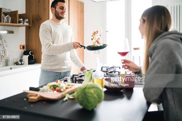 couple cooking food, tossing vegetables in frying pan - arremessar - fotografias e filmes do acervo