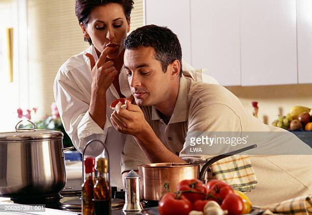 Couple cooking in kitchen, tasting pasta sauce