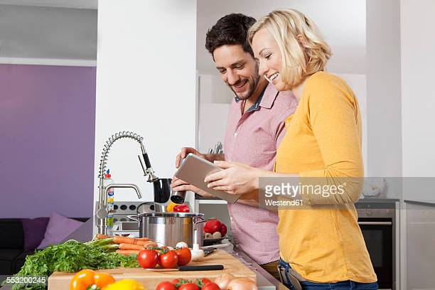 Couple cooking in kitchen using digital tablet
