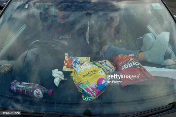 Couple cover their dashboard with snacks as they watch the movie Jaws during a drive-in cinema experience at Newcastle Airport on August 05, 2020 in...
