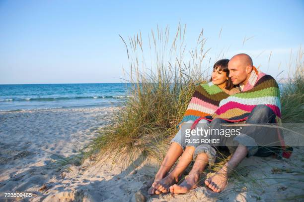 Couple covered with blanket on sand dune, Mallorca, Spain