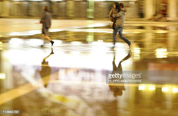 A couple cross a slightly flooded Piazza San Marco at high water in Venice on June 1 2011 AFP PHOTO / Filippo MONTEFORTE