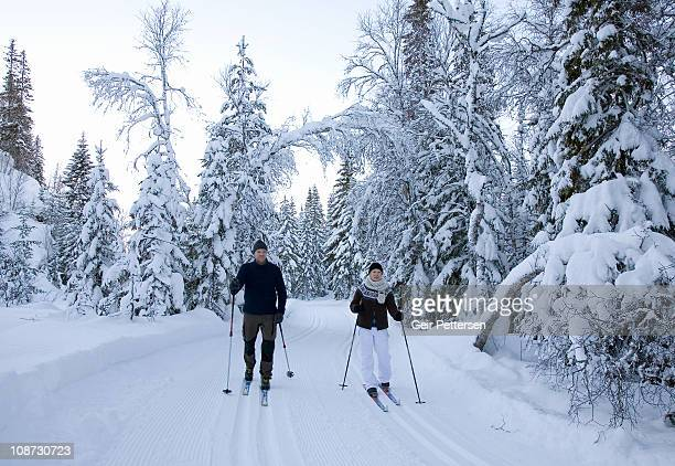 Couple cross-country skiing in forest