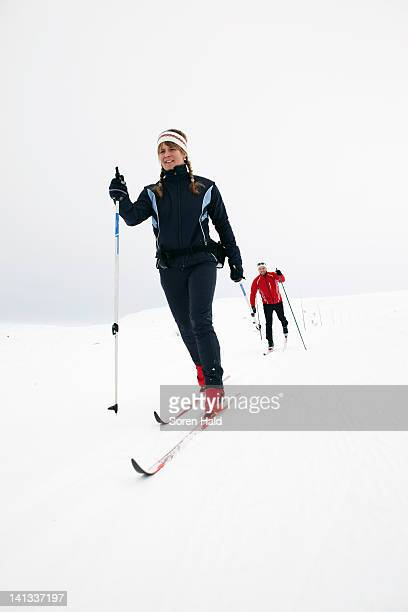 couple cross-country skiing in snow - langlaufen stockfoto's en -beelden