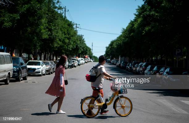 A couple crosses a street after buying goods at the Yilanyuan residential area which is under lockdown after a new COVID19 coronavirus outbreak near...