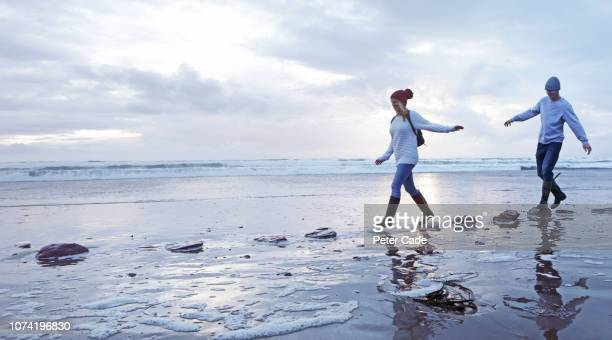 couple crossing stepping stones on beach - silver boot stock pictures, royalty-free photos & images