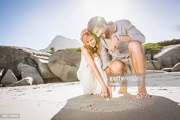 Couple crouching on beach drawing heart shape in sand