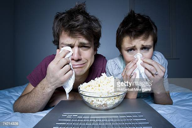 Couple crying with tissue and bowl of popcorn