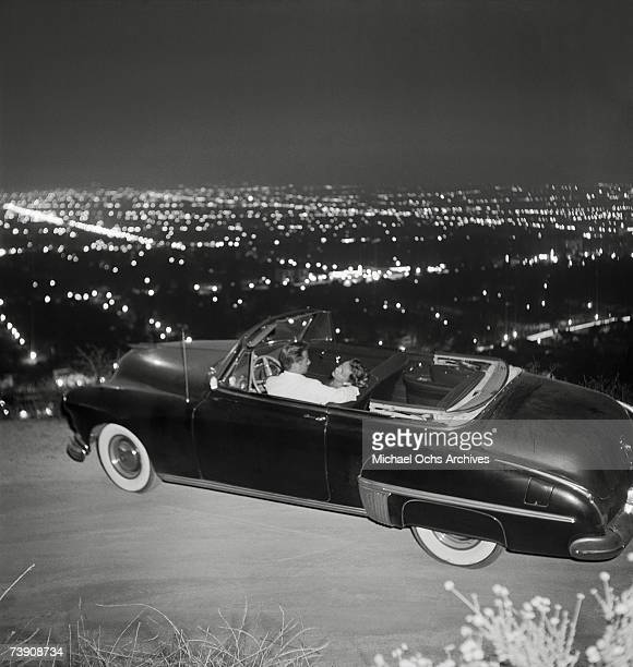 A couple cuddles up in a convertible overlooking Los Angeles from Mulholland Drive at night on July 15 1951 in Los Angeles California Hollywood