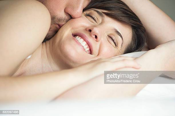 couple cuddling in bed, husband kissing wife - girlfriend photos stock photos and pictures