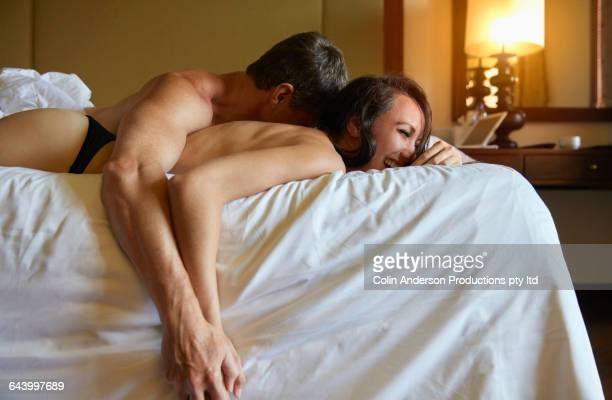 couple cuddling on bed - donne immagine foto e immagini stock