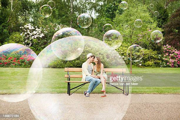 couple cuddling on bench, surrounded by bubbles. - romance stock pictures, royalty-free photos & images