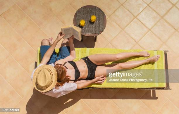 Couple cuddling on deck chair sharing book