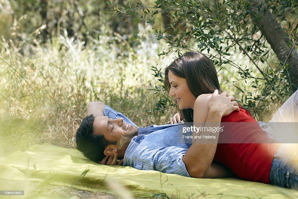 Couple Cuddling On Picnic Blanket Stock Photo