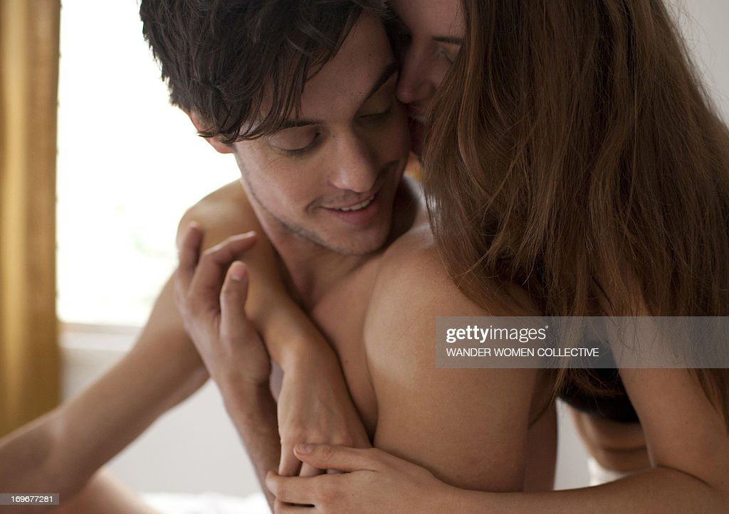 Couple cuddling sitting on bed : Stock Photo