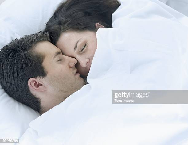 a couple cuddling under the bed sheets - romantic young couple sleeping in bed stock photos and pictures