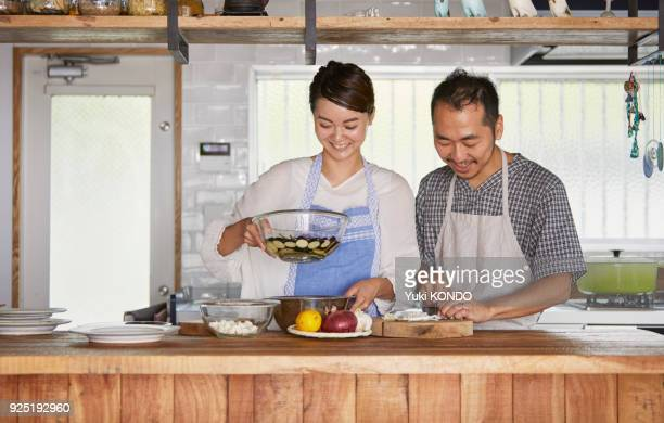 A couple cutting ingredients in the kitchen.