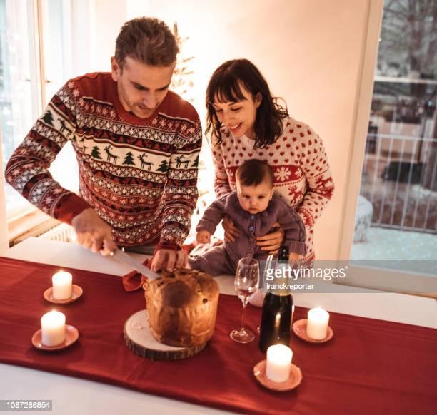 coppia taglio la torta panettone per il nuovo anno - panettone foto e immagini stock