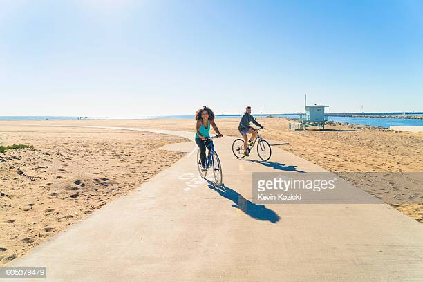 couple cycling along pathway at beach - la beach stock pictures, royalty-free photos & images