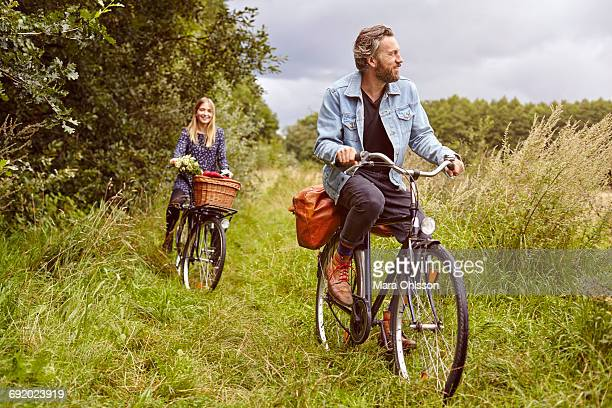 Couple cycling along rural path