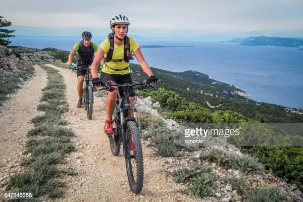 pareja ciclismo en costa - mountain bike fotografías e imágenes de stock