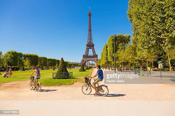 Couple cycling at the front of the Eiffel Tower in