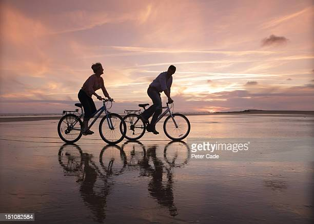 couple cycling on beach at sunset - twilight stock pictures, royalty-free photos & images