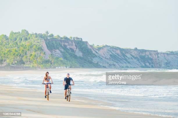 couple cycling on beach - trancoso imagens e fotografias de stock